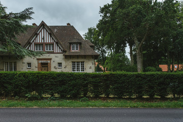 Country houses with green fences and streets in the region of Normandy, France. Beautiful countryside, lifestyle and typical french architecture, european country landscapes.