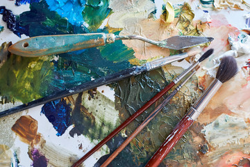 Artistic brushes and stacks lie on a palette with paints