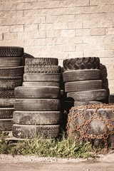 Stack of tyres leaning against wall