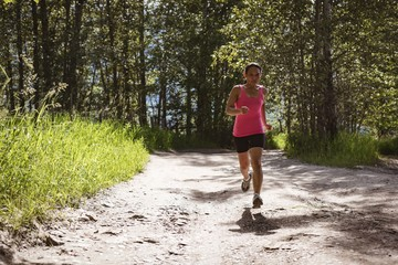 Fit woman jogging in forest road