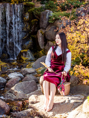 A young oriental girl with a basket in her hands is sitting besides a waterfall