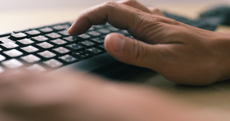 Man hands typing on a computer keyboard