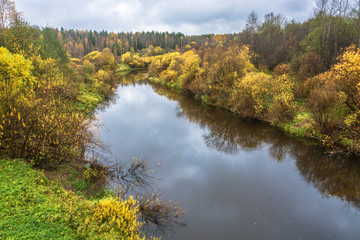A small river in the decoration of the yellow autumn trees.