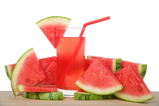 Glass of watermelon lemonade on a wood table surrounded by fruit. Red straw, slice of watermelon on side of cup, isolated on white background.
