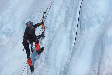 An ice climber makes his way on a frozen waterfall