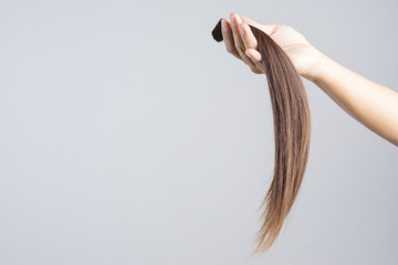Hand holding long hair donation for cancer patient