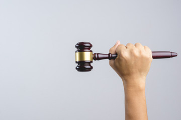 Hand holding wooden judge's gavel as a law or justice sign