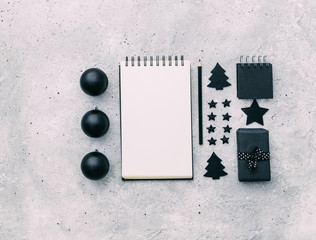 Black Christmas decor with notebook on grey background. flat lay, top view. Creative concept