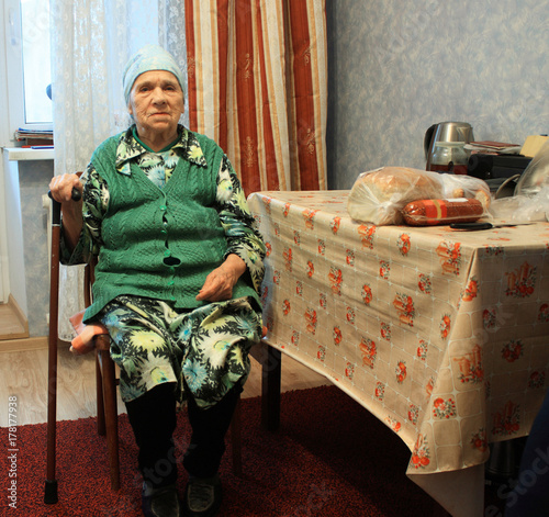 poverty old woman sitting on chair in the kitchen\