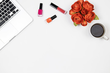 Flat lay home office desk. Woman workspace with laptop, peony flowers bouquet, lipstick, nail polish on white background. Top view feminine background.