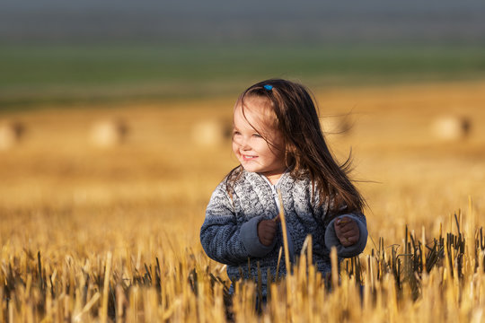 Happy 2 year old girl walking in a summer harvested field