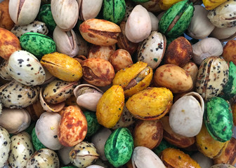 Background of spicy fiesta pistachios in multiple colors, yellow, green, gold