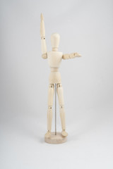 a wooden dummy posing with raised arms