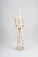 a wooden dummy posing with arms in front