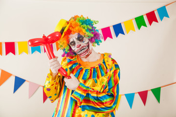 a terrible clown. Halloween. A crazy clown with a balloon in the form of a flower. Childish fear