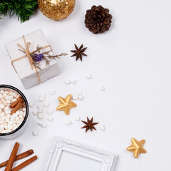 Christmas frame made of pine branches, pine cone, cup of hot chocolate drink with marshmallows, cinnamon sticks, anise star, gift box and golden ornaments on white background. flat lay, top view.