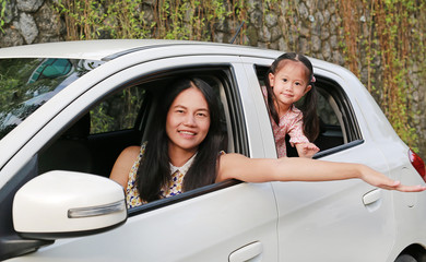 Happy young woman and her little child girl lying in a car. Family holidays concept.