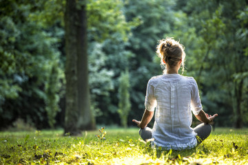 Foto op Plexiglas School de yoga Woman meditating and practicing yoga in forrest