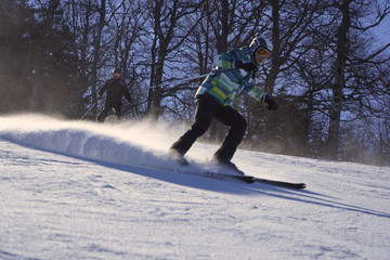Skier skiing downhill in high mountains against blue sky. Winter, ski resort