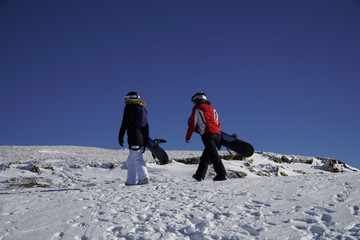 Adventure to winter sport. Snowboarders hiking at mountain. Looking for powder to freeride. Two girls with snowboard on the ski resort