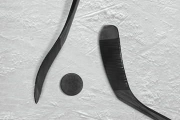 Two black sticks and ice hockey puck
