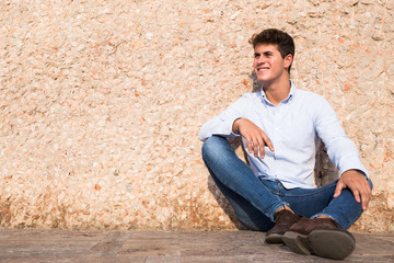 Happy-looking man in shirt and jeans sitting near beige wall on sunny day.