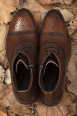 In autumn, the leaves are yellowed and Brown men's boots.