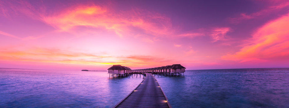 Luxury water bungalow in sunset time. Amazing colors and seascape view