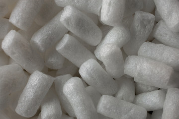 Plastic protective foam background and texture. Macro view of white packing foam background. Bubbly plastic protective granules. Closeup view of polystyrene for the protection of fragile packages