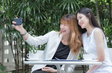 Two pretty young woman taking selfie from hand with smart phone and smiling in the garden, Urban life concept.