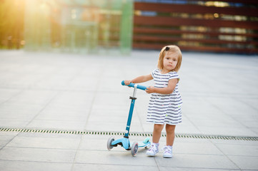 Portrait of a two year old girl with the scooter.