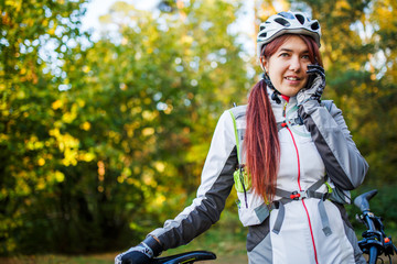 Woman in bicycle helmet talking on phone in autumn forest