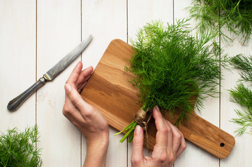 Top view of a woman's hand, fresh dill on a cutting board, knife and bunches of dill on a white wooden table. Fresh greens, seasoning, the process of cooking, a healthy lifestyle.