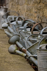old watering cans on a farm with old stone wall background
