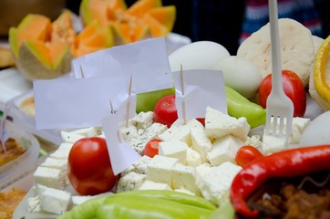 various delicious food on table for food street festival, cheese, tomato, peppers, pumpkin and plastic forks