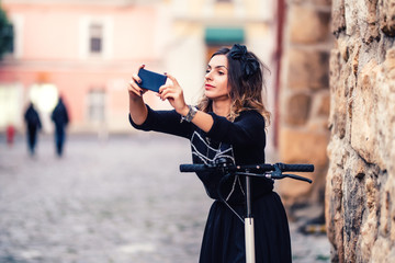 Happy girl taking selfie with camera while riding a kick scooter