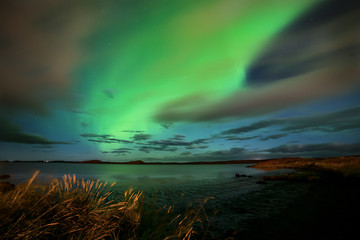 Aurora borealis on the lake shore. The radiance reflects in the water of the lake, in the background in the distance the silhouettes of the mountains. Lovely night view. Iceland.