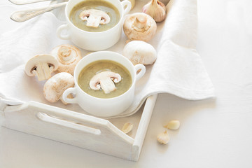 Two bowl with traditional mushroom soup cream on white table cloth