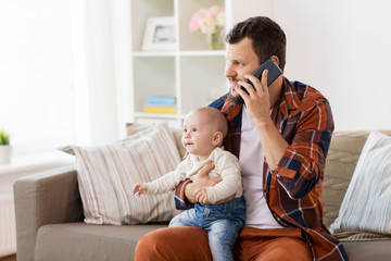 father with baby calling on smartphone at home