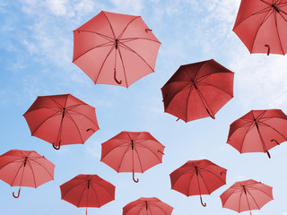 Many red umbrellas against sky. Viewed from below.