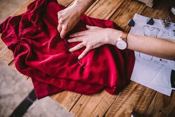 Close-up of female fashion designer working with textiles