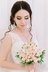 Beautiful bride perfect style. Wedding hairstyle make-up dress and bride's bouquet. Young attractive bride on chair in white room at studio