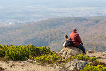 Father and son are sitting on a rock, on top of a mountain. View from the back.
