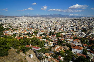 Panorama view of Athens cityscape from Acropolis showing white buildings architecture, mountain, trees, blue sky and floating white cloud background