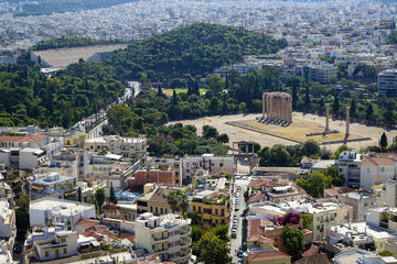 View of Athens cityscape from Acropolis showing ancient ruin, buildings architecture, urban streets, green trees and white city background