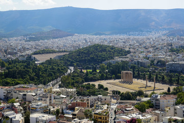 View of Athens city from Acropolis showing ancient ruin, buildings architecture, urban streets, green trees and mountain background