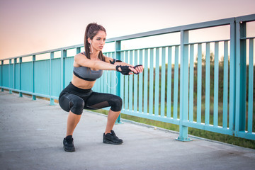 Young athletic woman doing squat exercises on sidewalk over the bridge outdoors.