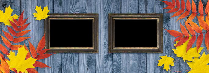 Autumn background with two photo frames and autumnal leaves on wooden boards in rustic style