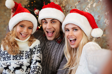 Close-up of young family in Santa's hat having fun while taking selfie