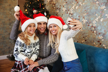 Young family in Santa's hat having fun while taking selfie on mobile phone